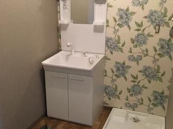 大きな花柄のアクセントクロスとウッド調クッションフロアが素敵な洗面所。